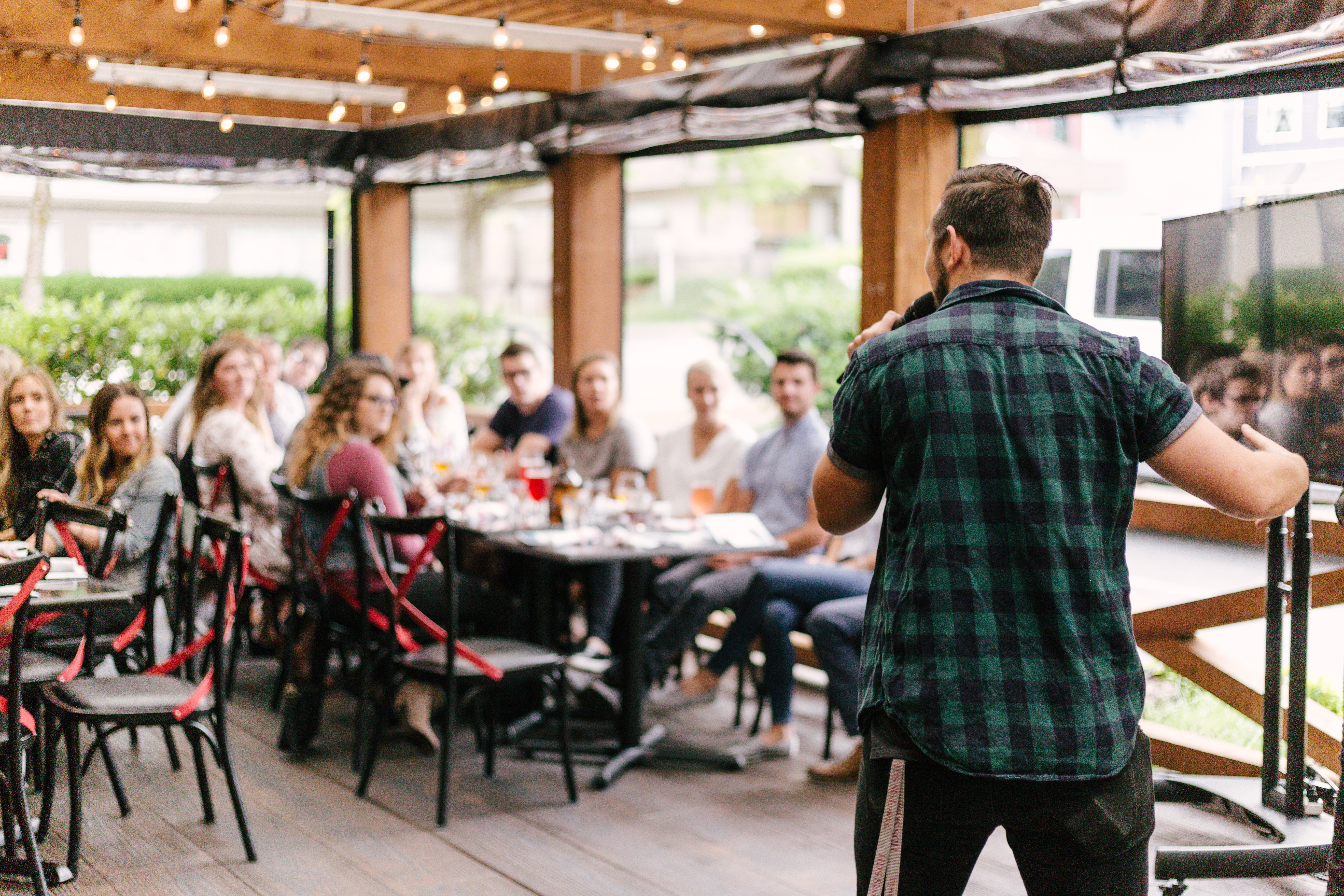 A man in his twenties in a green plaid shirt with short sleeves stands at the front of a room full of people. He is speaking into a microphone. It appears to be a restaurant, with chairs set up at long tables. There are several people in their twenties or thirties sitting at the tables, looking at the man speaking.