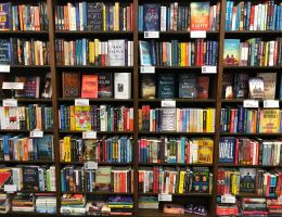 A bookshelf completely full of books fills the image. None of the titles or spines are legible, but the books are a range of colours and appear to be mostly novels.]